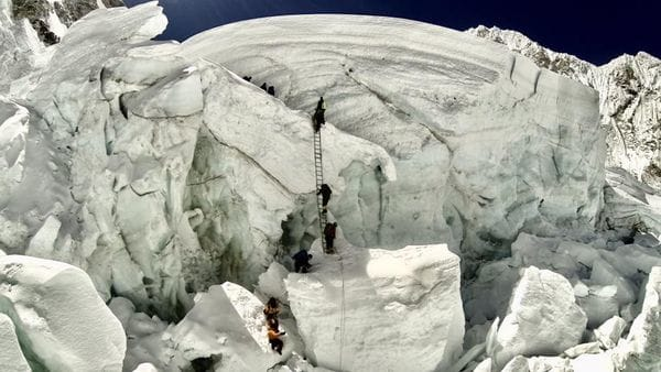 Escaladores utilizan una escalera para trepar por el lado nepalés camino a la cima del monte Everest (AFP Photo / Ryan S. Davy)