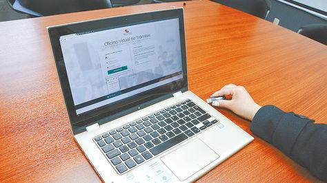 Proceso. Una funcionaria introduce el token (similar al USB) para realizar la firma digital, en AgeTIC.