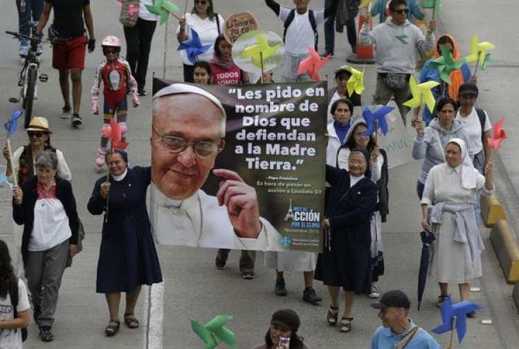Un grupo de feligreses camina con un pancarta del papa Franscisco.(AP Photo/Fernando Vergara, File)