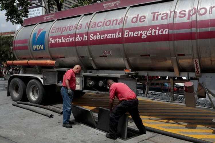 Trabajadores llenas los suministros de gasolina en una estación de servicio en Venezuela. (REUTERS/Marco Bello)