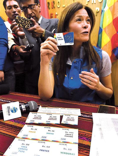 Dispositivo. Ballivián muestra la tarjeta y los vales de productos frescos.