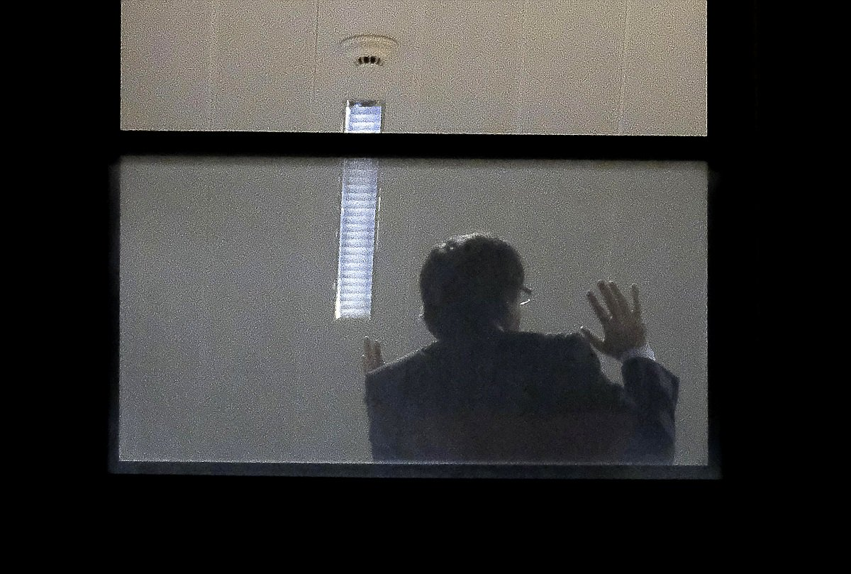 A man believed to be Carles Puigdemont gestures inside the public prosecutor