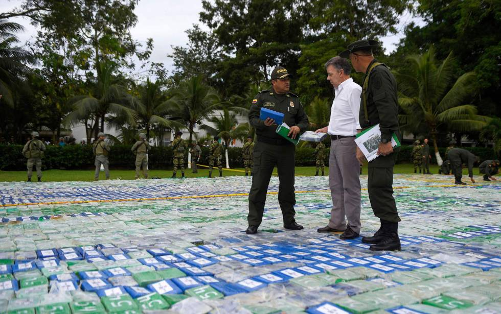 El presidente de Colombia, Juan Manuel Santos, y dos agentes sobre las más de 12 toneladas de cocaína incautada. rn rn rn