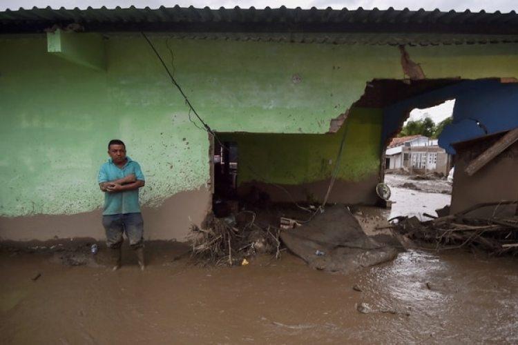 Un hombre está parado en su casa destruida en Corintio, Valle. / AFP PHOTO / LUIS ROBAYO