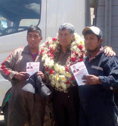 El postulante al TCP Pastor Mamani junto con personas que sostienen volantes con su imagen.