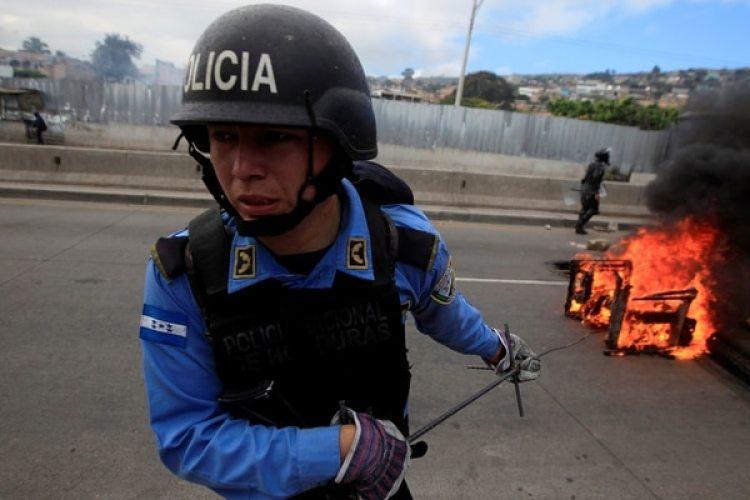 Un policía retira un objeto en llamas de una barricada opositora (Reuters)