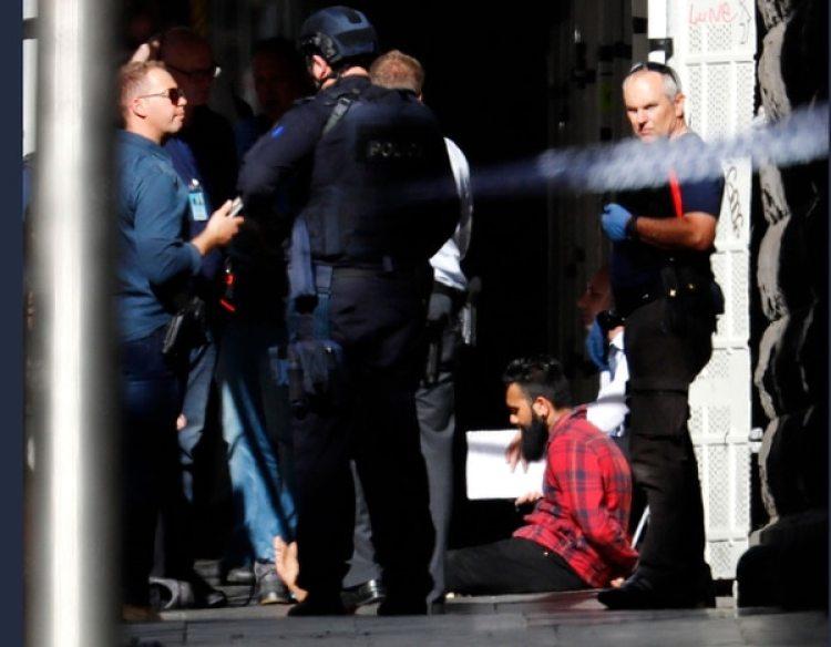 Uno de los detenidos, el supuesto conductor del vehículo, esposado y custodiado. (Herald Sun)