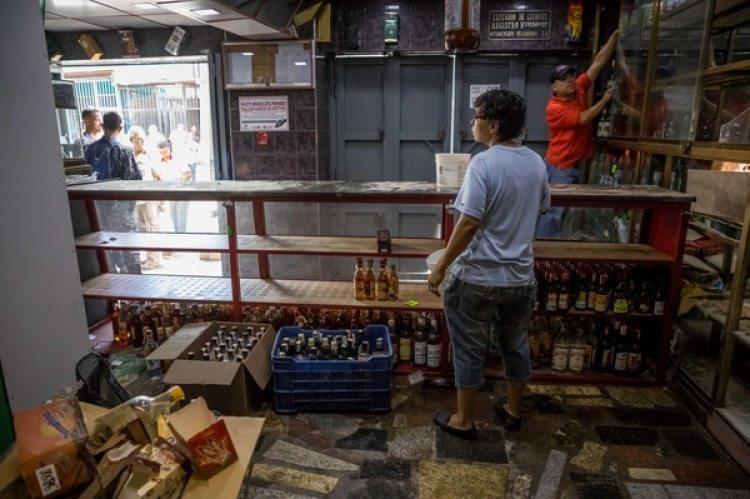 Un trabajador de una licorera que fue saqueada en horas de la madrugada en el sector La Vega saca productos del local comercial en Caracas (Venezuela).(EFE/Miguel Gutiérrez)