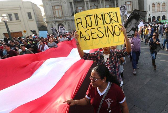 "Protesters march as one holds a sign that reads, ""Fujimori killer"", after Peruvian President Pedro Pablo Kuczynski pardoned former President Alberto Fujimori in Lima, Peru, December 25, 2017. REUTERS/Mariana Bazo"