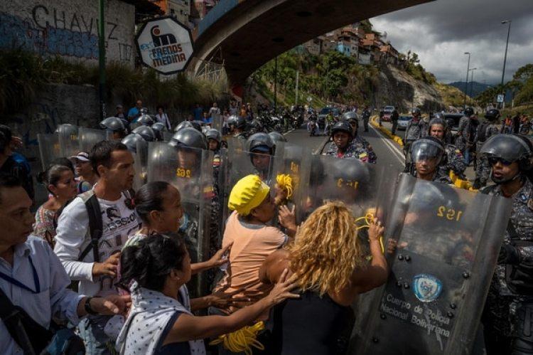 Un grupo de personas protesta frente a miembros de la Policía Nacional Bolivariana (PNB) en Caracas (EFE/Miguel Gutiérrez)