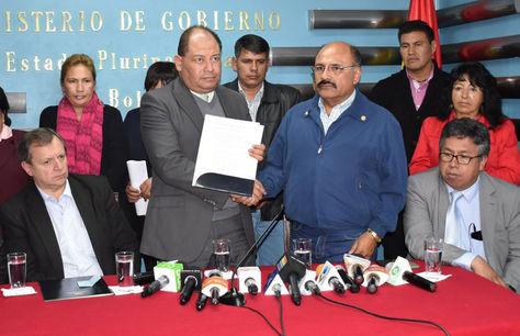 Carlos Romero, ministro de Gobierno, y Aníbal Cruz, presidente del Colegio Médico de Bolivia, sellan con un saludo el convenio entre Gobierno y médicos.