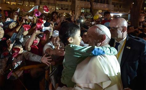 El Papa Francisco abrazando a un niño mientras es recibido por una multitud de fieles a su llegada a la sede de la Nunciatura Apostólica en Lima, Perú.