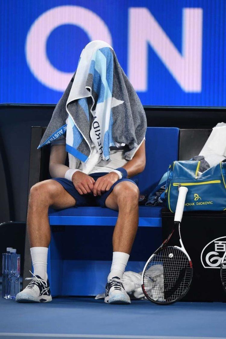 Novak Djokovic se cubre la cabeza con una toalla durante su partido de la cuarta ronda del Abierto de Australia contra el surcoreano Hyeon Chung, en Melbourne, Australia(EFE/ Lukas Coch)