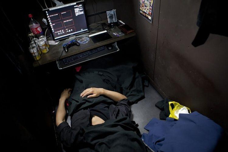 """Fumiya, de 26 años, duerme con una manta sobre su cara para bloquear las luces fluorescentes que permanecen encendidas durante la noche. Dice que vivir en un cibercafé """"no es tan malo""""."""