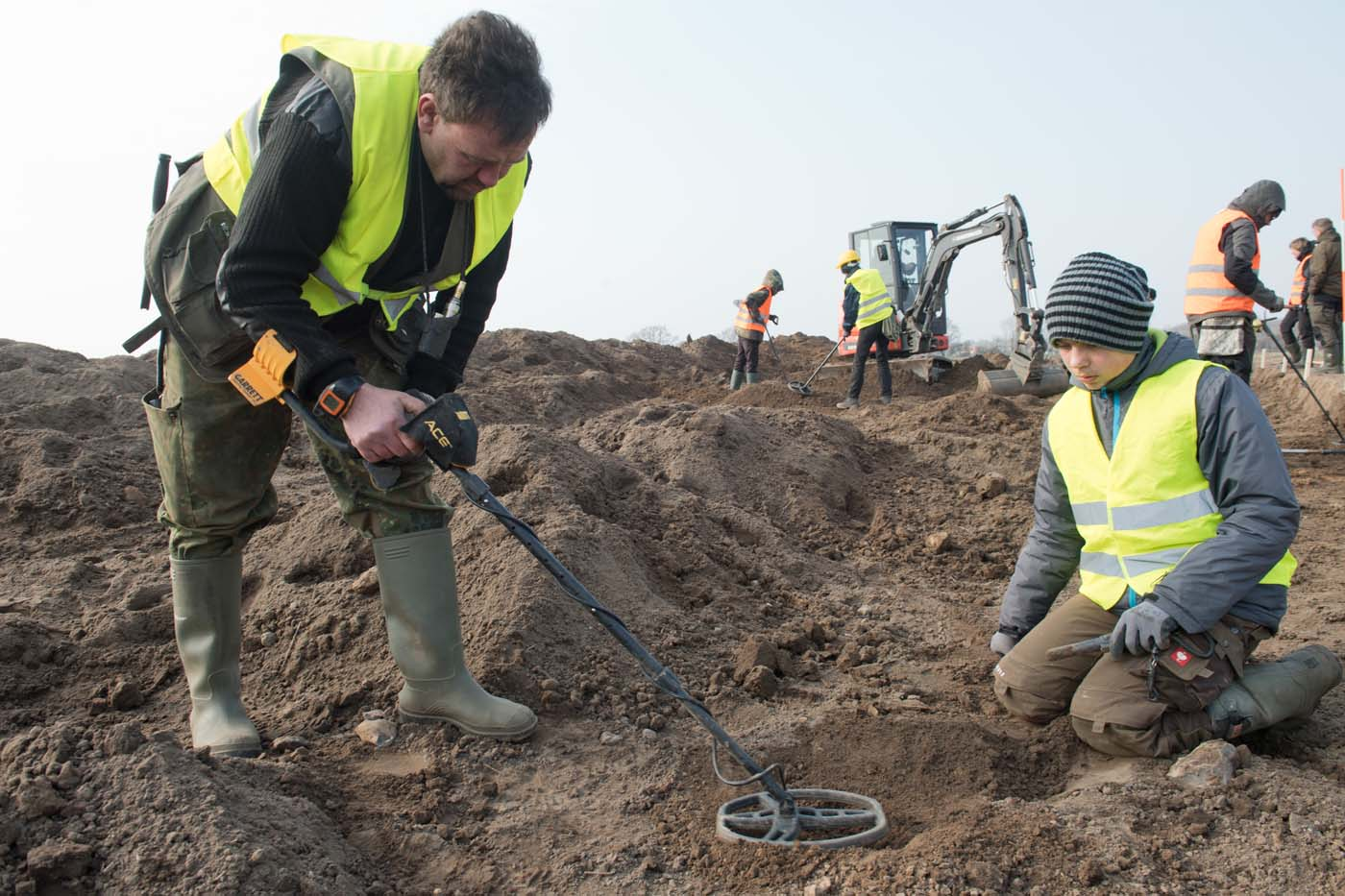"Amateur archaeologist Rene Schoen (L) and 13-year-old student Luca Malaschnichenko look for a treasure with a metal detector in Schaprode, northern Germany on April 13, 2018. The 13-year-old boy and the hobby archaeologist have unearthed a ""significant"" trove in Germany which may have belonged to the legendary Danish king Harald Bluetooth who brought Christianity to Denmark. A dig covering 400 square metres (4,300 square feet) that finally started over the weekend by the regional archaeology service has since uncovered a trove believed linked to the Danish king who reigned from around 958 to 986. Braided necklaces, pearls, brooches, a Thor"