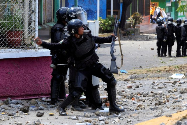 A riot policeman throws a rock toward university students during a protest against the reforms that implement changes to the pension plans of the Nicaraguan Social Security Institute (INSS) in Managua, Nicaragua April 19,2018.REUTERS/Oswaldo Rivas