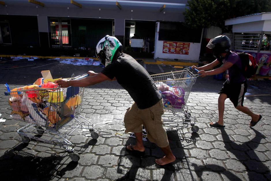 Nicaraguenses con bienes robados de una tienda durante saqueos en Managua, Nicaragua. (Reuters)