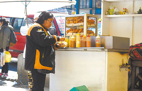Riesgo. Un ciudadano consume una tucumana en un puesto de la Pérez Velasco.