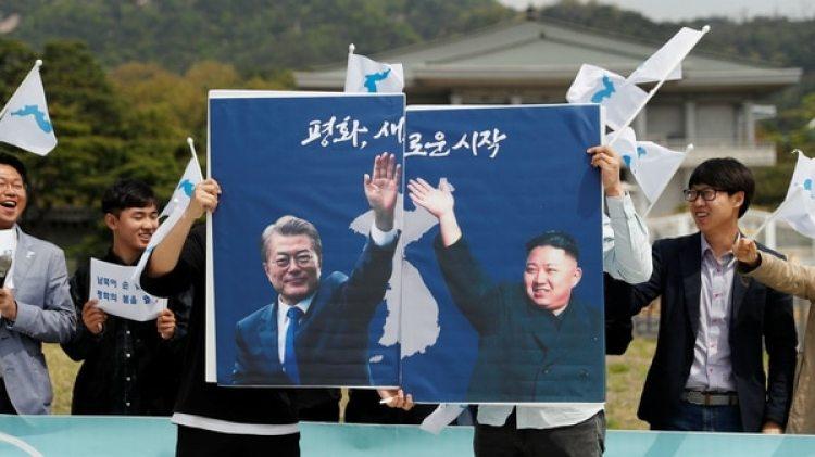 Estudiantes con posters del presidente surocoreano Moon Jae-in y del dictador norcoreano Kim Jong-un durante una manifestación a favor de la reunificación de las dos Coreas (Reuters)