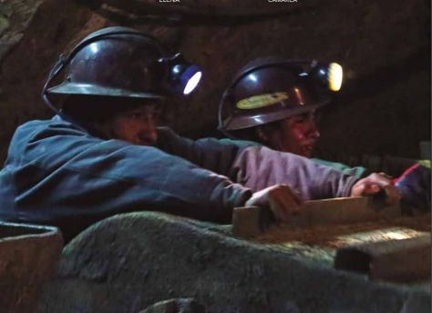 Dos trabajadores mineros empujan un carro.