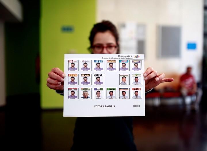 Una mujer muestra en el centro de votación de Madrid, la boleta electoral. Nicolás Maduro aparece 10 veces, el resto de los candidatos 7. AFP