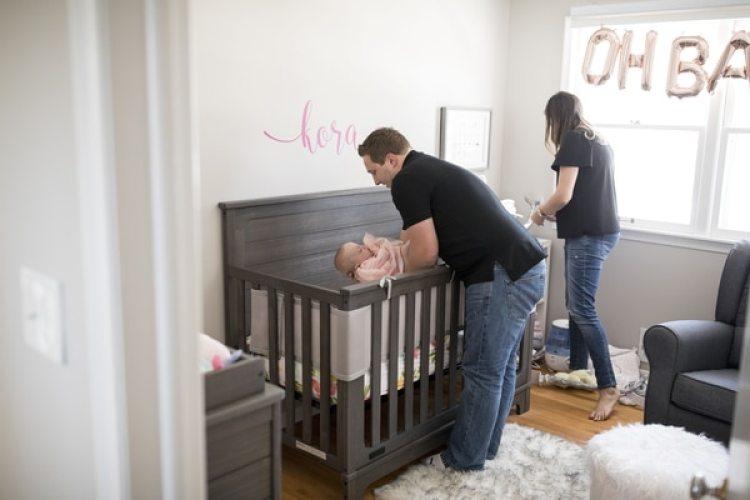 Ben Kellner coloca a Kora, que ahora tiene 7 meses, en su cuna (The Washington Post / Jenn Ackerman)