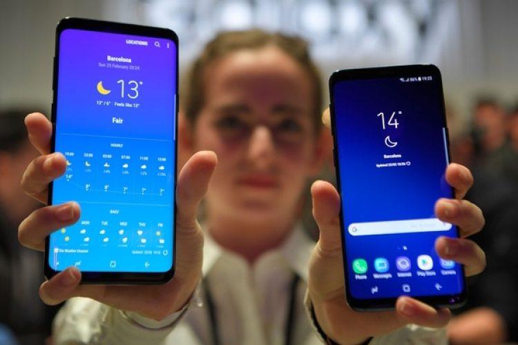 Una empleada muestra los dispositivos más recientes de Samsung, los smartphones Galaxy S9 y S9Plus (AFP)
