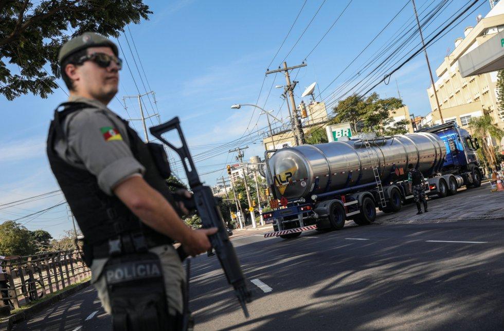 Con menos bloqueos y una mayor salida de gasolina desde las refinerías, los autobuses y transportes de mercancías empezaron a retomar su actividad. En la imagen, un policía vigila la entrada a una estación de servicio en Porto Alegre (Brasil), el 29 de mayo de 2018.