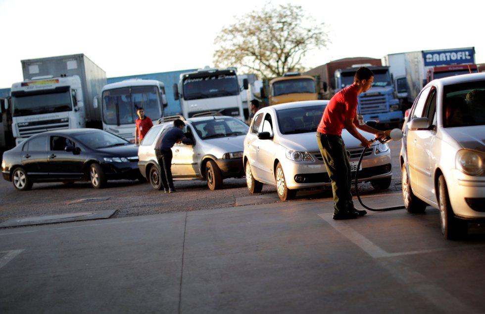 En el estado de Sao Paulo, la gran terminal petrolera de Ribeirao Preto volvió a funcionar después de que los camioneros levantaran el bloqueo. En la imagen, un empleado de una estación de servicio echa gasolina en un vehículo en Brasilia (Brasil), el 29 de mayo de 2018.