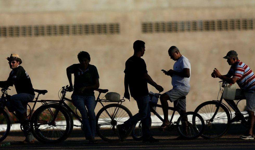 Un grupo de personas esperan con sus bicicletas su turno para echar gasolina en el exterior de una estación de servicio en Brasilia, el 29 de mayo de 2018.