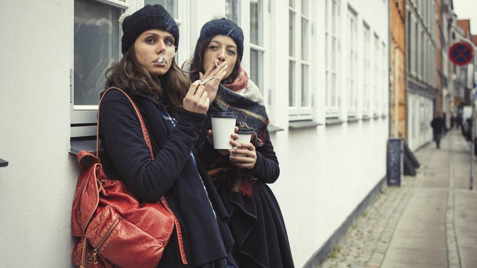 Mujeres fumando y bebiendo café.