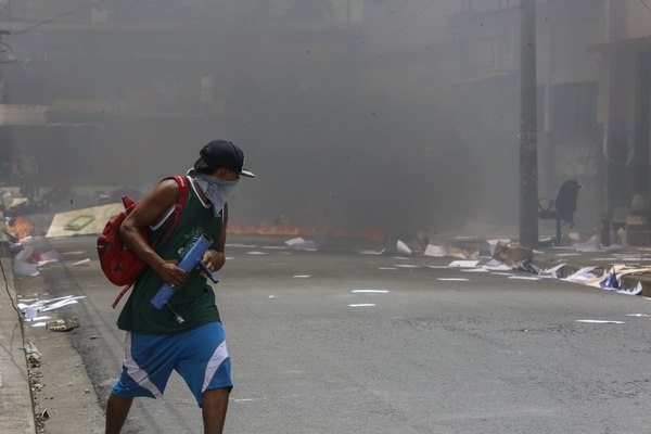 A masked protester runs near a burning barricade in the Monimbo neighborhood during clashes with police, in Masaya, Nicaragua, Saturday, June 2, 2018. More than 110 people have been killed in Nicaragua during clashes between forces loyal to President Daniel Ortega and opposition groups. (AP Photo/Alfredo Zuniga)