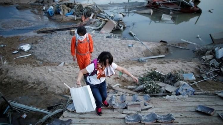 Los residentes locales caminan en un área inundada en la ciudad de Mabi en Kurashiki (REUTERS/Issei Kato)