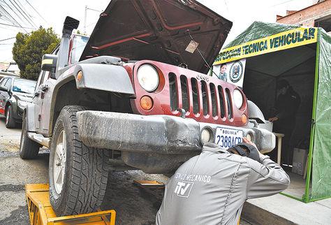 Trabajo. Un mecánico realiza la inspección técnica a un vehículo.