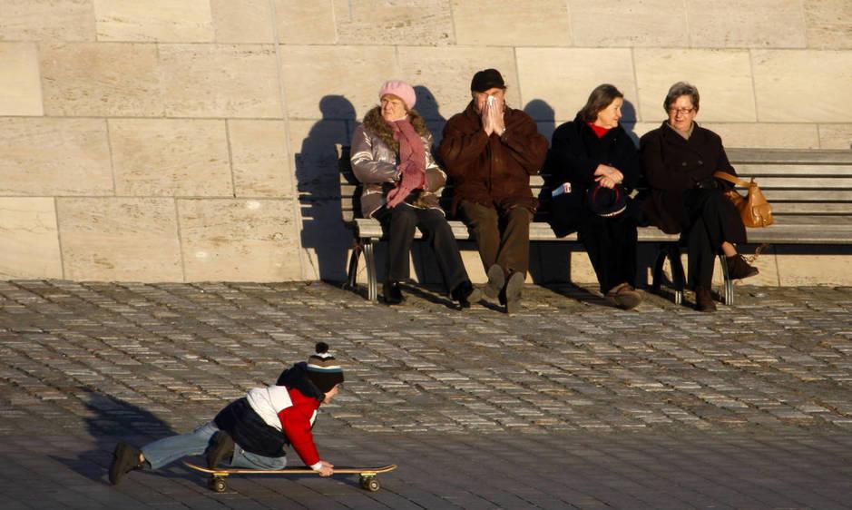 Varios pensionistas observan a un niño con un monopatín, en Berlín. (Reuters)