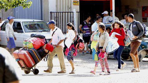 Ciudadanos venezolanos esperan un bus en la ciudad colombiana de Cúcuta.