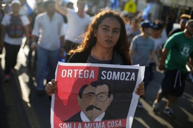 Una manifestante sostiene un cartel durante una protesta enManagua en donde compara a Daniel Ortega con el dictador nicaragüense Somoza. (REUTERS/Jorge Cabrera)