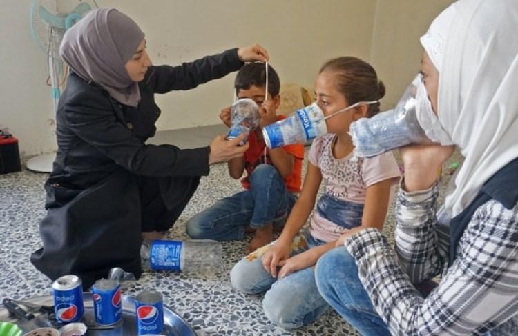 Una mujer improvisa unas máscaras de gas con botellasde plástico para proteger a sus hijos(AFP PHOTO / Muhammad HAJ KADOUR)