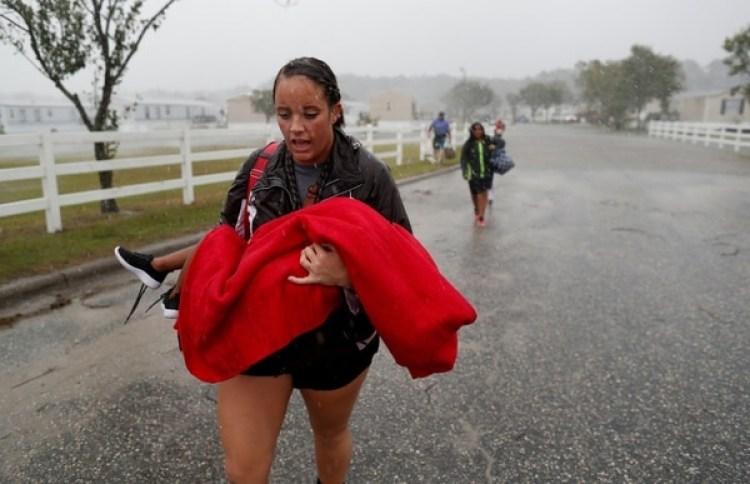 Una mujer carga a un menor durante las evacuaciones en Carolina del Norte (Reuters)