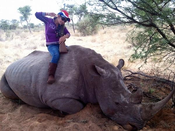 Una de las mujeres contratada por Lemtongthai para obtener numerosos permisos de caza de rinocerontes, junto a su presunto trofeo. (The New York Times/Julian Rademeyer)