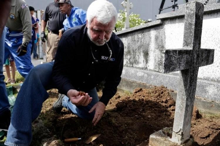El arqueólogo marítimo James Delgado inspecciona los escombros en la tumba de Julius H. Kroehl antes de exhumar sus restos en el cementerio Amador en el barrio de El Chorrillo, en la ciudad de Panamá (AP Foto/Arnulfo Franco)