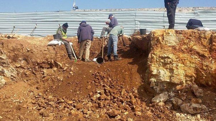 Trabajadores excavan en la fosa común