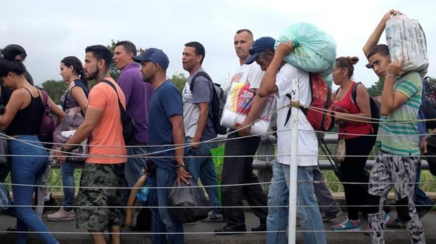 Un grupo de venezolanos cruzan el puente de Simón Bolivar, que separa la frontera de Venezuela con Colombia, tras haberse aprovisionado en Cúcuta
