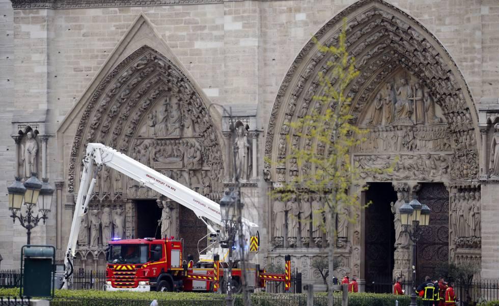 Grupos de bomberos trabajan ante la fachada de la catedral de Notre Dame, esta mañana.