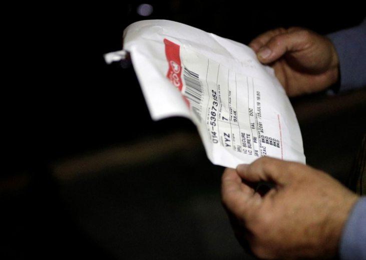 Un policía revisa un documento que venía en el cargamento donde estaba el oro y los metales.(Reuters)