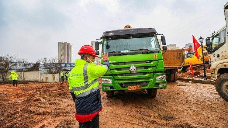 Uno de los cientos de camiones que acuden a llevarse la tierra que remueven las palas mecánicas en Wuhan (Chinatopix vía AP)