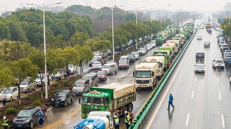 Los camiones esperan su turno para cargar la tierra que será extraída del terreno donde se construirá el centro de salud (Foto de STR/ AFP/ China OUT)