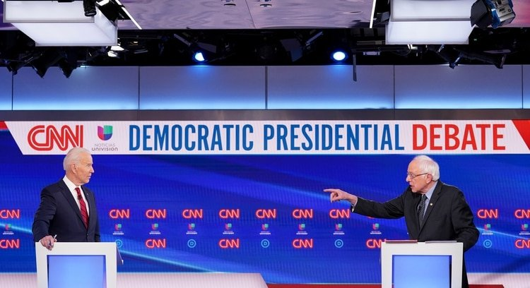 Democratic U.S. presidential candidate former Vice President Joe Biden listens as Senator Bernie Sanders speaks during the 11th Democratic candidates debate of the 2020 U.S. presidential campaign, held in CNN's Washington studios without an audience because of the global coronavirus pandemic, in Washington, U.S., March 15, 2020. REUTERS/Kevin Lamarque
