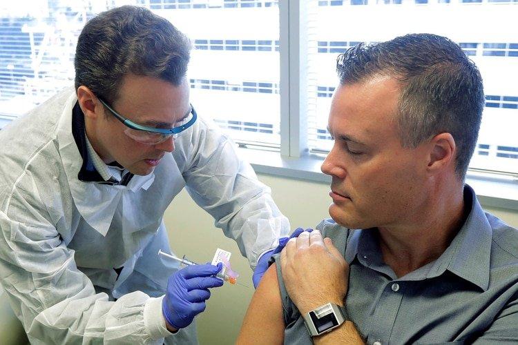 El farmacéutico Michael Witte le suministra a Neal Browning (derecha) una inyección en el ensayo clínico de la primera etapa del estudio de seguridad de una posible vacuna para COVID-19 (AP)