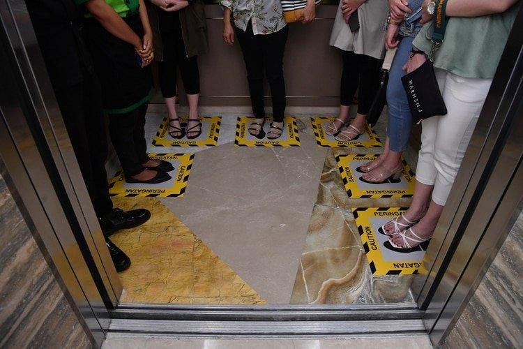 Visitantes a un edificio en Indonesia mantienen la distancia obligatoria al subir al ascensor (Antara Foto/Zabur Karuru/ via REUTERS)